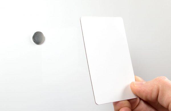 Dubbelsidigt vitt vändbart plastkort med metall som fäster mot magnet